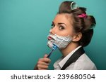 Small photo of Cute funny brunette woman in hair curlers wearing men shirt and tie undone posing with foam on face, isolated on blue background, role gender reversal concept