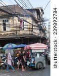 Small photo of BANGKOK - DECEMBER 10: typical street scene in an older district of the city with unidentified people on December 10, 2014 in Bangkok. typical for Bankok is the power supply line aboveground