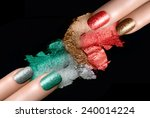 Close Up of Women Hands with Painted Nails and Coordinating Mineral Eye Shadows Swatches in Festive Colors on Black Background - stock photo