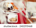 Haute cuisine concept. Ice cream brownie sundae with chocolate sauce and slices of date plum on white plate. Close up. Indoor shot - stock photo