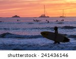 Surfers Silhouetted Against A...