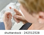 senior woman putting a plaster... | Shutterstock . vector #242512528