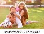 family lying in pile up on... | Shutterstock . vector #242759530