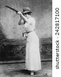 Small photo of Woman posed with shotgun for trapshooting in 1914. In the 19th century trap shooters used the abundant Passenger Pigeon as their targets, until it became extinct from human overkill.