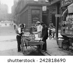Men eating fresh clams from a pushcart peddler in the Italian neighborhood of Mulberry Bend in New York City. Ca. 1900 photograph by Byron.