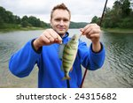 Happy fisherman presents perch, caught big fish - stock photo