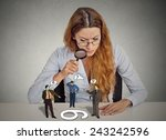 Small photo of Businesswoman with glasses sitting at desk skeptically looking at arguing people through magnifying glass isolated grey office wall background. Human face expression, attitude. To each its own concept