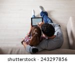 Young couple sitting on floor and using tablet.Relaxing.View from above. - stock photo