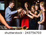 Small photo of Happy friends drinking shots by the dj booth at the nightclub