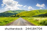 composite landscape with abandoned asphalt road rolls through meadows with flowers going to high  mountains - stock photo