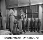 Small photo of Agriculture Department fabric technician examines the cotton stockings that would replace those made by Japanese silk, after FDR froze all Japanese credits in the United States. July 1941.