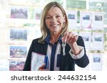 Small photo of Estate Agent In Office Holding Keys To Property