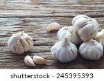 garlic on the wooden background  | Shutterstock . vector #245395393