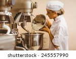 baker pouring flour into large... | Shutterstock . vector #245557990