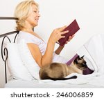 Stock photo happy female pensioner with cat reading book and smiling in bed 246006859
