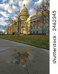 Capital building reflecting in a puddle with dramatic clouds - stock photo