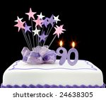 Fancy cake with number 90 candles.  Decorated with ribbon and star-shapes, in pastel tones on black background. - stock photo