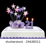 Cake with number 21 candles.  Decorated with ribbons and star-shapes, in pastel tones over black background. - stock photo