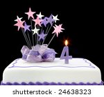 Fancy cake with number 4 candle.  Decorated with ribbons and star-shapes, in pastel tones over black background. - stock photo
