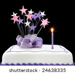 Fancy cake with a single lit candle.  Pastel tones, with ribbons and stars. - stock photo