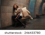 Small photo of Girl sitting on a bench facing away from the toy bear, they quarreled and sadness.