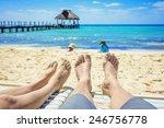 Tan Feet Of A Couple On Lounge...