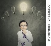 Stock photo portrait of cute little boy with thinking style while looking at the bright lightbulb 246836800