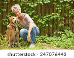 Stock photo smiling elderly woman sitting with a dog in a garden in summer 247076443