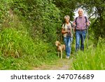 Stock photo happy senior couple walking with dog on a hiking trail 247076689