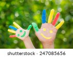 Smiley On Hands Against Green...