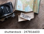 """text """"The World Awaits"""" and book, travel, tour, tourism concept"""