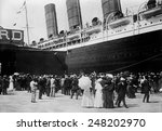 Small photo of HMS Lusitania at New York dock in 1907. She is met by a crowd on her a starboard side.
