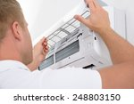 Small photo of Portrait Of A Young Man Adjusting Air Conditioning System