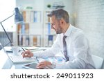 elegant businessman analyzing... | Shutterstock . vector #249011923