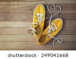 Yellow Gym Shoes On A Wooden...