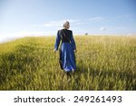 An Old Order Amish woman in a blue dress and black cape and apron walks in a grassy field on a sunny afternoon