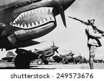 Chinese soldier guards a line of American P-40 fighter planes, ca. 1942. The shark-face fighters of the