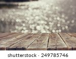 wood board table in front of summer landscape of sparkling lake water. background is blurred
