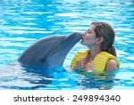 Happy Woman Kissing Dolphin In...