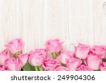 Stock photo valentines day background with pink roses over wooden table top view with copy space 249904306