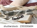 Small photo of Book and glasses on bed close-up