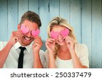 Small photo of Attractive young couple holding pink hearts over eyes against wooden planks