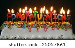 cake with lit candles spelling congratulations - stock photo