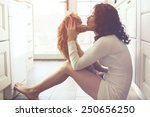 Stock photo young lady kissing cat on the floor at the kitchen at home 250656250