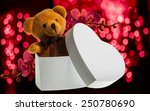 brown toy bear in white heart box with red orchid flower on blur background - stock photo