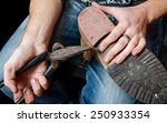 young shoemaker repairing a old ...