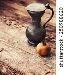 Small photo of Old style coper jug with pomegranate on old wooden table background