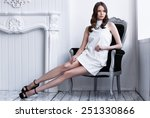 Fashion shot of young beautiful woman in white short dress sitting in antique armchair