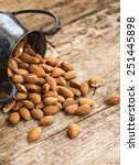 Small photo of Almonds in a coper old style vase, on old wooden table background