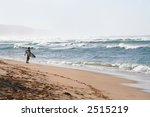 A surfer on the beach holding a board - stock photo